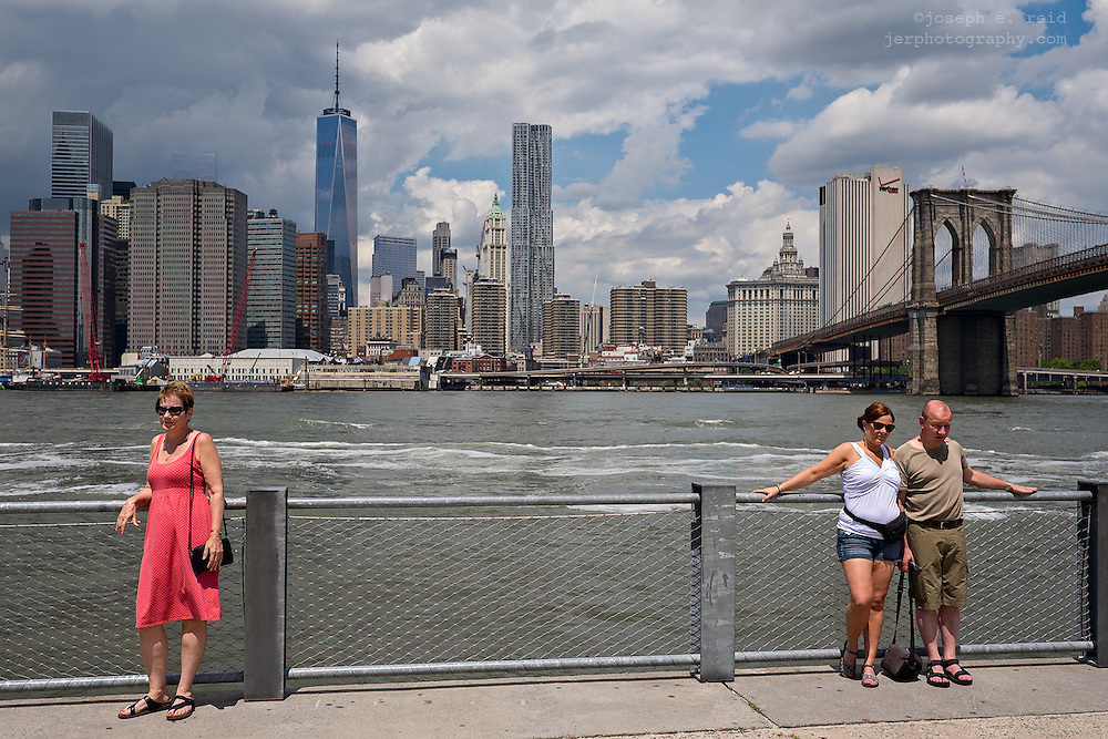 Tourists posing for snapshots on Brooklyn waterfront, Brooklyn, NY, US