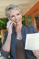 Elegant mature woman using mobile phone holding brochure