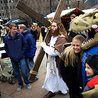 """While visitors pose for photographs with a Santa Claus dinosaur,  Michael Grant, 28, """"Philly Jesus,"""" walks through the Christmas Village in LOVE Park towards the nativity scene after carrying this 12 foot cross 8 miles through North Philadelphia to Center City as part of a Christmas walk to spread the true message of the holiday in Philadelphia, PA on December 20, 2014.  As many as a half dozen others joined him for numerous miles as he trekked southward down Broad Street.  Some shouted """"Praise Jesus!"""" and """"Thank you for doing this!""""at the sight.  Nearly everyday for the last 8 months, Grant has dressed as Jesus Christ, and walked the streets of Philadelphia to share the Christian gospel by example.  He quickly acquired the nickname of """"Philly Jesus,"""" which he has gone by ever since. REUTERS/Mark Makela (UNITED STATES)"""
