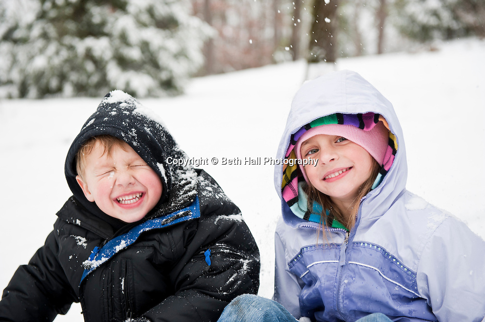 A boy and girl sit in the snow.