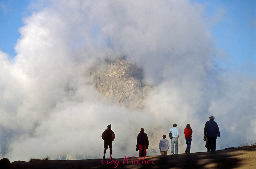 Visitors to Glacier Point watch a clearing spring storm.  May 1990