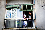 A mother and her child, wearing a cook costume, watch the parade in Scampia from their window