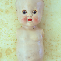 Face and limbless body of vintage baby doll with big staring blue eyes and red lips and slightly scuffed and soiled