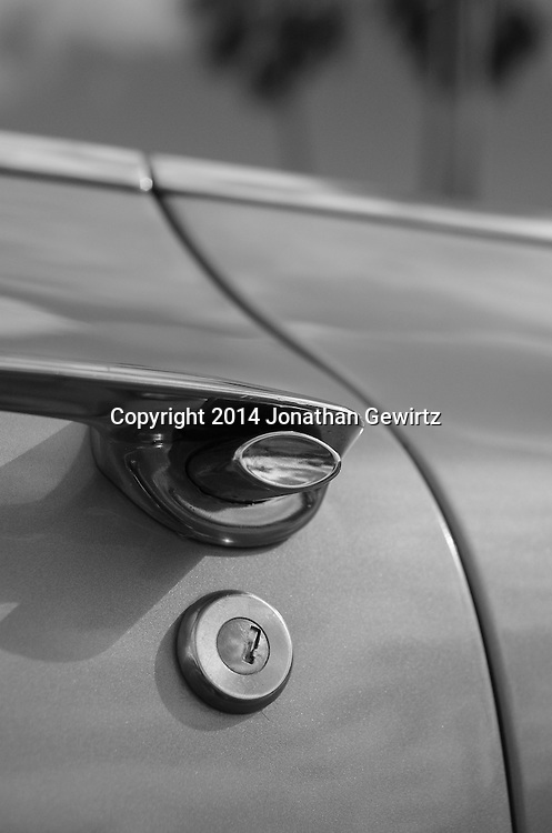 Black and white view of the keyhole and door handle of a 1960 Cadillac convertible. WATERMARKS WILL NOT APPEAR ON PRINTS OR LICENSED IMAGES.