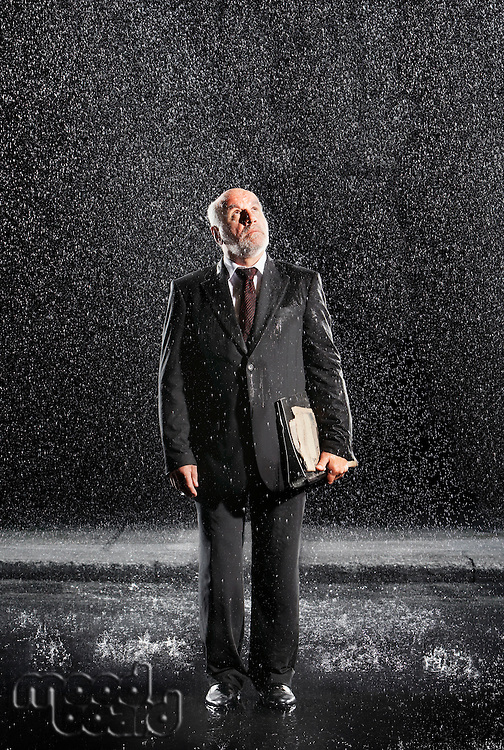 Rain falling on businessman Without Protection looking to sky