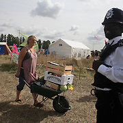 The Camp for Climate Change UK 2007<br /> The camp was a camp set up to highlight protests against a proposed third runway at Heathrow, destroying nearby villages and to put the spotlight on climate change issues.  A black police man watches over the camp on site.