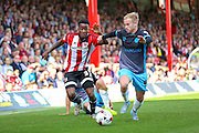 Brentford Midfielder Josh Clarke and Sheffield Wednesday Midfielder Barry Bannan battle for the ball during the Sky Bet Championship match between Brentford and Sheffield Wednesday at Griffin Park, London, England on 26 September 2015. Photo by Phil Duncan.