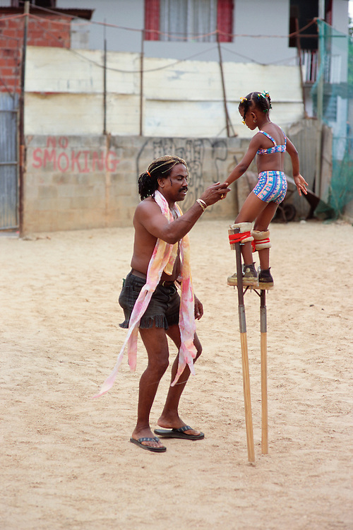 "Trinidad and Tobago ""MOKO JUMBIES: The Dancing Spirits of Trinidad"".(Dragon Glen de Souza teaches five-year-old N'Neka Pompey on the first day she graduated from three-foot to four-and-a-half-foot stilts. The stilts can weigh from 8 to 10 pounds each, for the 3-foot stilts, and as much as 25 pounds or more for each 6-foot stilt.).A photo essay about a stilt walking school in Cocorite, Trinidad..Dragon Glen de Souza founded the Keylemanjahro School of Art & Culture in 1986. The main purpose of the school is to keep children off the streets and away from drugs..He first taught dances like the Calypso, African dance and the jig with his former partner Cathy Ann Samuel.  Searching for other activities to engage the children in, he rediscovered the art of stilt-walking, a tradition known in West Africa as the Moko Jumbies , protectors of the villages and participants in religious ceremonies. The art was brought to Trinidad by the slave trade and soon forgotten..Today Dragon's school has over 100 members from age 4 and up..His 2 year old son Mutawakkil is probably the youngest Moko Jumbie ever. The stilts are made by Dragon and his students and can be as high as 12-15 feet. The children show their artistic talents mostly at the annual Carnival, which today is unthinkable without the presence of the Moko Jumbies. A band can have up to 80 children on stilts and they have won many of the prestigious prizes and trophies that are awarded by the National Carnival Commission. Designers like  Peter Minshall , Brian Mac Farlane and Laura Anderson Barbata create dazzling costumes for the school which are admired by thousands of  spectators. Besides stilt-walking the children learn the limbo dance, drumming, fire blowing and how to ride  unicycles..The school is situated in Cocorite, a suburb of Port of Spain, the capital of Trinidad and Tobago..all images © Stefan Falke"