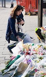 © under license to London News Pictures.  25/03/201. A woman lays flowers outside the SUJU nightclub in the Wiltshire town of Swindon, where personal assistant Sian O'Callaghan, was last seen alive. Her murdered body was found yesterday by police. Picture credit should read: London News Pictures