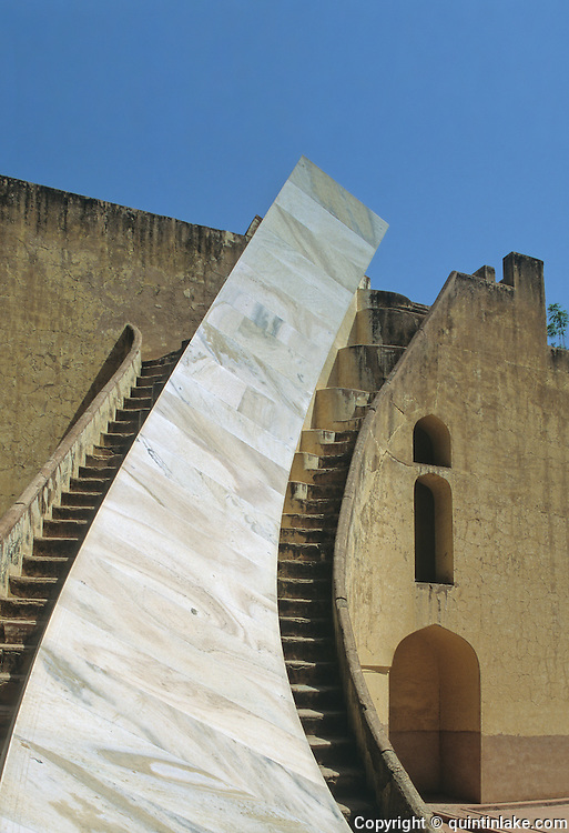 Marble astronomical scale of the Samrat Yantra (the Supreme Instrument) is the world's largest sundial, standing 27 meters tall. Its shadow moves visibly at 1 mm per second at the Jantar Mantar, a collection of architectural astronomical instruments, built by Maharaja Jai Singh II between 1727 and 1734. Jaipur, India, 2002