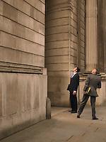 Two businessmen facing monumental building