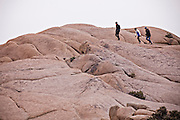 Hikers walk along Jumbo Rocks in Joshua Tree National Park, California.