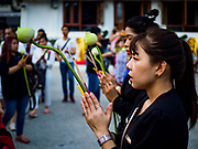 "01 MARCH 2018 - BANGKOK, THAILAND:  People pray at Wat Pathum Wanaram in central Bangkok. Many people go to temples to perform merit-making activities on Makha Bucha Day, which marks four important events in Buddhism: 1,250 disciples came to see the Buddha without being summoned, all of them were Arhantas, or Enlightened Ones, and all were ordained by the Buddha himself. The Buddha gave those Arhantas the principles of Buddhism. In Thailand, this teaching has been dubbed the ""Heart of Buddhism.""    PHOTO BY JACK KURTZ"