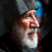 "Portrait of Armenian priest - clergyman. He is one of the speakers at ""We Cannot Forget, We Will Not Forget"" is the theme of the Commemeorian at 44th Street and Times Square, lisening to other speaker waiting his turn to get up and speak."