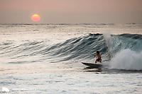 Surfer at sunset on the North Shore of O'ahu, Hawaii.