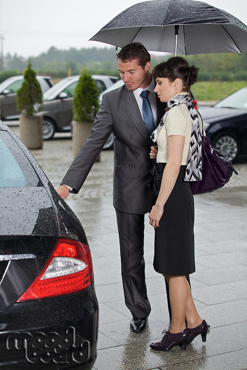 Young man opening door of car for woman