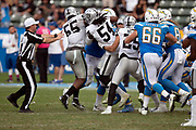 NFL side judge Alex Kemp (55) tries to break it up as a fight breaks out between teammates after Los Angeles Chargers tight end Antonio Gates (85) is hit low by Oakland Raiders linebacker Marquel Lee (55) on a fourth quarter play in which the Raiders LB gets hit with a 15 yard roughing penalty during the NFL week 5 regular season football game against the Oakland Raiders on Sunday, Oct. 7, 2018 in Carson, Calif. The Chargers won the game 26-10. (©Paul Anthony Spinelli)