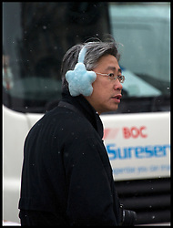 A man wearing ear warmers in  Parliament Square after a Snowfall in  London,  Friday January 18, 2013. Photo By Andrew Parsons / i-Images