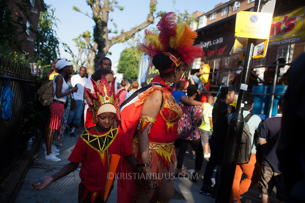 A young boy dressed up is taken by the hand away from the music and the party and he is not happy about it. The Notting Hill Carnival has been running since 1966 and is every year attended by up to a million people. The carnival is a mix of amazing dance parades and street parties with a distinct Caribbean feel.