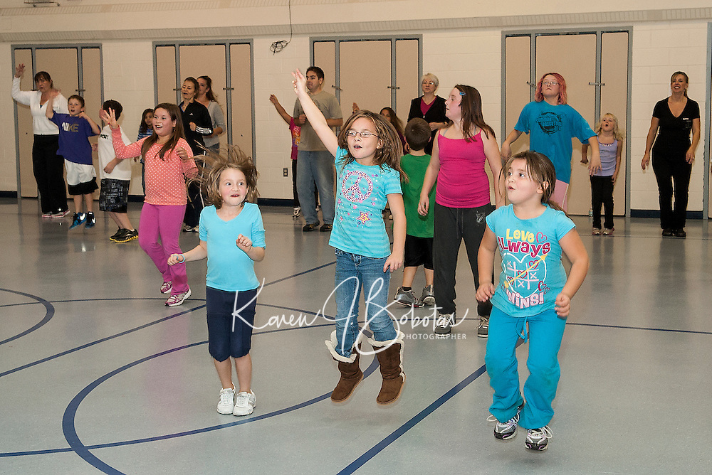 Carley Trainor,Teanna Hollins and her sister Savannah get into their groove during the Family Fun Fitness night at Woodland Heights Elementary School Tuesday evening.  (Karen Bobotas/for the Laconia Daily Sun)