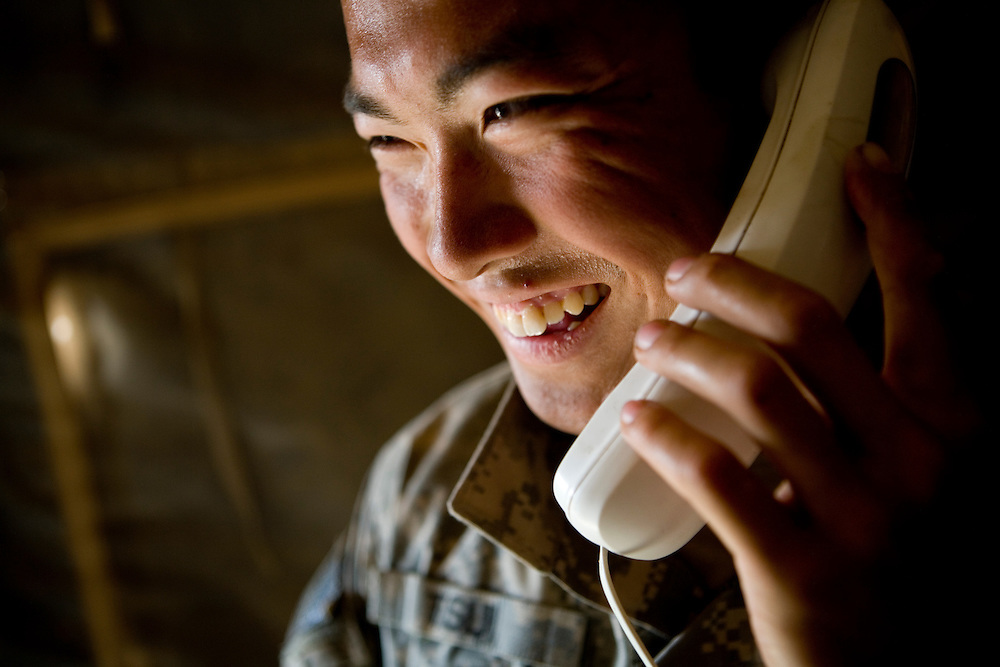 Specialist Ying Kit Tsui of the 82nd Airborne's 1/508 Alpha Company talks to his wife for the first time in three weeks after returning to Forward Operation Base Diablo after a mission in remote Kandahar province, Afghanistan on Wednesday, March 28, 2007.