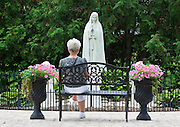 A visitor to the Shrine of Our Lady of Good Help in Champion, Wis., sits in front of a statue of Our Lady of Fatima July 19. (Sam Lucero photo)