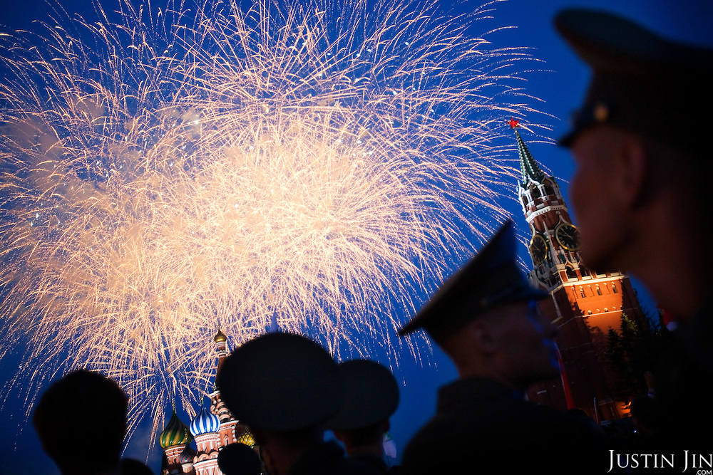 Russian soldiers watch fireworks on the Red Square in Moscow, with the St. Basil's Cathedral in the background.