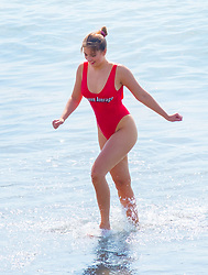 © Licensed to London News Pictures. 21/04/2018. Aberystwyth, UK. As the period of unusually warm weather continues across much of the UK, a young woman in a red swimsuit takes a dip in the sea in the hot sunshine on the Saturday afternoon. Photo credit: Keith Morris/LNP
