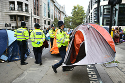 © Licensed to London News Pictures. 08/10/2019. London, UK. Police remove tents belonging to Extinction Rebellion activists outside DEFRA in Westminster. Activists have converged on Westminster for a second day, blockading roads in the area and calling on government departments to 'Tell the Truth' about what they are doing to tackle the Emergency. Photo credit: Ben Cawthra/LNP