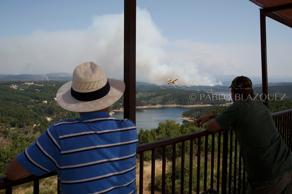 LEIRIA, PORTUGAL - JUNE 20:  Men watch firefighter planes battling a fire after a wildfire took dozens of lives on June 20, 2017 in Mega Fundeira village, near Picha, in Leiria district, Portugal. On Saturday night, a forest fire became uncontrollable in the Leiria district, killing at least 62 people and leaving many injured. Some of the victims died inside their cars as they tried to flee the area.  (Photo by Pablo Blazquez Dominguez/Getty Images)