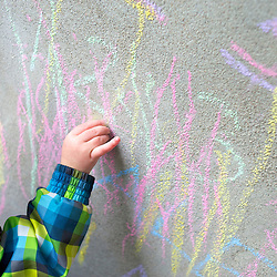 Toddler writing on a concrete wall with chalk. Photographe: Marc Lapointe, Sainte-Thérèse, Blainville, Québec. Studio de photo marclapointephoto.