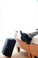 Low section of businessman lying on bed beside luggage in hotel room