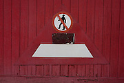 A No Pedestrians entry sign on the red door of a local garage business.
