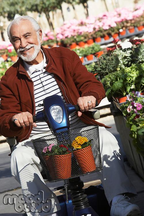 Elderly man on motor scooter in garden center
