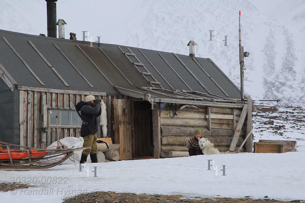 Frode Skar and Ragnhild Røsseland stand outside trapper's hut where they are living off the land for two years in remote Austfjorden in Svalbard, Norway.