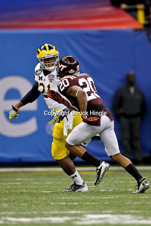 January 3, 2012; New Orleans, LA, USA; Michigan Wolverines wide receiver Junior Hemingway (21) is covered by Virginia Tech Hokies cornerback Jayron Hosley (20) during the Sugar Bowl at the Mercedes-Benz Superdome. Michigan defeated Virginia 23-20 in overtime. Mandatory Credit: Derick E. Hingle-US PRESSWIRE