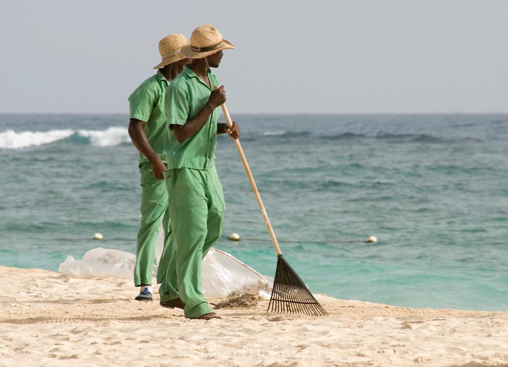 Resort walkers raking up garbage on the beach in Punta Cana