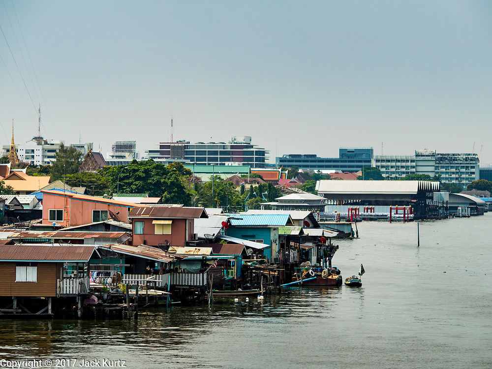 03 APRIL 2017 - BANGKOK, THAILAND: Housing along the Chao Phraya River south of the Krung Thon Bridge in Bangkok. This is one of the first parts of the riverbank that is scheduled to be redeveloped. The communities along the river don't know what's going to happen when the redevelopment starts. The Chao Phraya promenade is development project of parks, walkways and recreational areas on the Chao Phraya River between Pin Klao and Phra Nang Klao Bridges. The 14 kilometer long promenade will cost approximately 14 billion Baht (407 million US Dollars). The project involves the forced eviction of more than 200 communities of people who live along the river, a dozen riverfront  temples, several schools, and privately-owned piers on both sides of the Chao Phraya River. Construction was  scheduled to start in early 2016 but had been pushed back to late 2017. There has been very little public input on the planned redevelopment.             PHOTO BY JACK KURTZ
