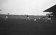Galway player runs while in possession of the ball as Galway players falls to the ground during All Ireland Senior Gaelic Football Championship Final Dublin V Galway at Croke Park on the 22nd September 1963. Dublin 1-9 Galway 0-10.