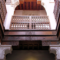 Medersa Ben Youssef Small Courtyard in Marrakech, Morocco <br /> This is one of seven inner courtyards of Medersa Ben Youssef.  Behind the elaborately carved balconies are the former student dormitories. The rooms were so small and sparse that they resembled cells. The school closed in 1960. After an extensive restoration, the madrasa reopened as a tourist attraction.  Medersa Ben Youssef is one of the best examples of Moorish architecture in the city.
