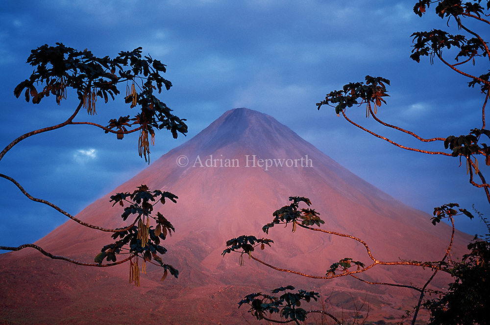 There are times when even landscape photography requires fast reactions; on this clear afternoon, as the sun closed on the horizon, its rays warmed the ordinarily-grey Arenal Volcano to an orange-brown and then  a deep red. Seconds later the sun disappeared and all the color on the volcano faded with it.<br />