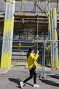 Woman wearing yellow walks past matching coloured scaffolding on London's Southbank.