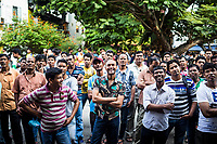 A crowd of men gather to watch a movie playing on an outdoor television in Little India, Singapore.