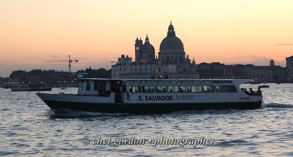 A water taxi in the lagoon and The Salute in the background at sunset in Venice, Italy. April 2002.