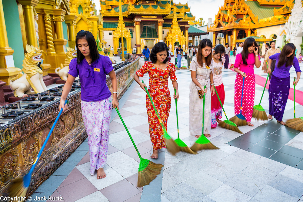 """15 JUNE 2013 - YANGON, MYANMAR:  Women who volunteer to """"make merit"""" clean the grounds of Shwedagon Pagoda. The Shwedagon Pagoda is officially known as Shwedagon Zedi Daw and is also called the Great Dagon Pagoda or the Golden Pagoda. It is a 99 metres (325ft) tall pagoda and stupa located in Yangon, Burma. The pagoda lies to the west of on Singuttara Hill, and dominates the skyline of the city. It is the most sacred Buddhist pagoda in Myanmar and contains relics of the past four Buddhas enshrined: the staff of Kakusandha, the water filter of Koṇāgamana, a piece of the robe of Kassapa and eight strands of hair fromGautama, the historical Buddha. The pagoda was built between the 6th and 10th centuries by the Mon people, who used to dominate the area around what is now Yangon (Rangoon). The pagoda has been renovated numerous times through the centuries. Millions of Burmese and tens of thousands of tourists visit the pagoda every year, which is the most visited site in Yangon. PHOTO BY JACK KURTZ"""