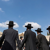 Israel, Jerusalem, Circle of Orthodox Jewish men join hands while dancing by Western Wall during religious celebration