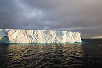Iceberg glowing in a ray of sunlight, Antarctica. Seascape and icescape photography wall art, fine art photography prints, stock images.