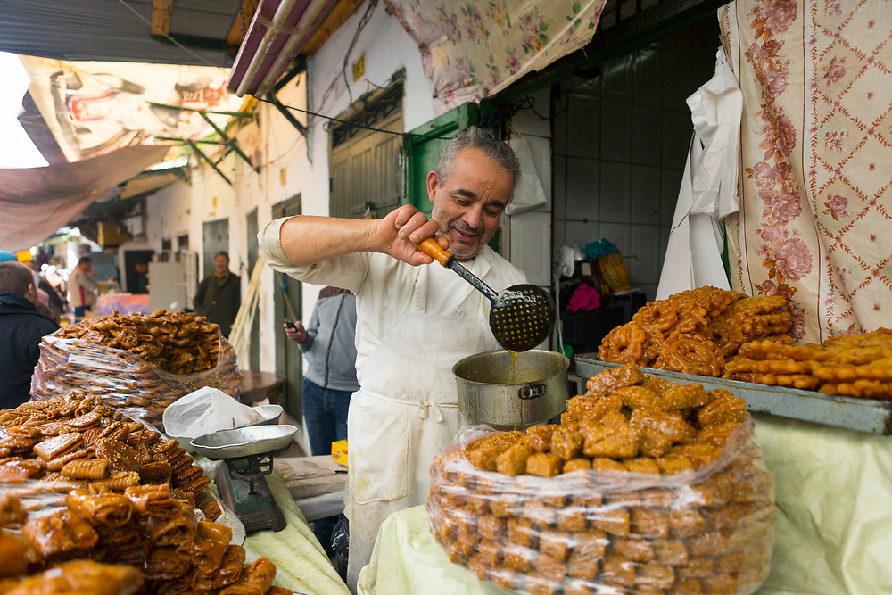 Moroccan chebekia and birouat street food stall, Tetouan, Rif region of Northern Morocco, 2016-04-05.<br /><br />Chebakia is a sweet dough pastry infused with rosewater rolled to resemble a rose, deep fried until golden, glazed with generous amounts of honey and sprinkled with toasted seasame seeds. <br /><br />Briouats can be sweet or savoury and the term generally refers to small pastry parcels which are deep fried and this instance, glazed with honey and sprinkled with toasted seasame seeds. The sweet version birouats are often filled a sweetened almond and rosewater paste in the centre.