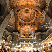 The ornately decorated interior of the prayer hall of the New Mosque (Yeni Cami) in Istanbul. Situated in the busy Eminonu quarter of Istanbul, at the southern end of the Galata Bridge, the New Mosque (or Yeni Cami) dates to around 1665. It's large prayer hall is decorated in the distinctive Ottoman imperial style.