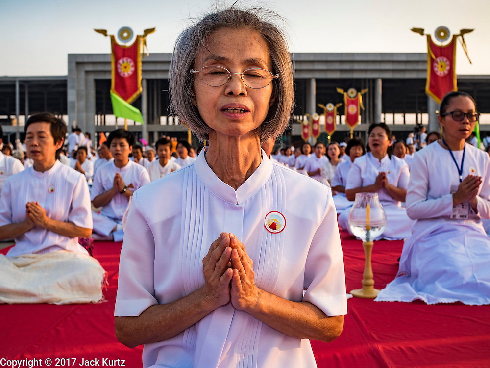 """11 FEBRUARY 2016 - KHLONG LUANG, PATHUM THANI, THAILAND:  People pray during the Makha Bucha Day service at Wat Phra Dhammakaya.  Makha Bucha Day is a public holiday in Cambodia, Laos, Myanmar and Thailand. Many people go to the temple to perform merit-making activities on Makha Bucha Day, which marks four important events in Buddhism: 1,250 disciples came to see the Buddha without being summoned, all of them were Arhantas, or Enlightened Ones, and all were ordained by the Buddha himself. The Buddha gave those Arhantas the principles of Buddhism. In Thailand, this teaching has been dubbed the """"Heart of Buddhism."""" Wat Phra Dhammakaya is the center of the Dhammakaya Movement, a Buddhist sect founded in the 1970s and led by Phra Dhammachayo. Makha Bucha Day is one of the most important holy days on the Thai Buddhist calender.     PHOTO BY JACK KURTZ"""